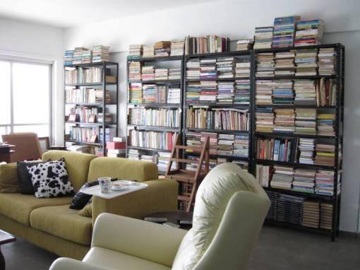 Aí estão os 1.800 livros, que já subiram para as estantes. Delas, somente a primeira à esquerda está arrumada. nas outras empilhei os volumes, que terão forçosamente que passar por uma triagem ara poderem caber nas prateleiras. Isso se eu conseguir me livrar deles.