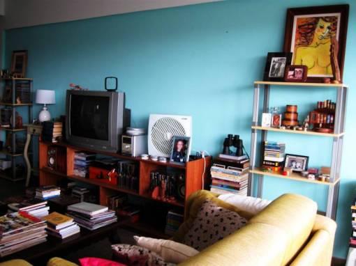 A parede em frente às estantes é azul: eu adoro essa cor. Gosto de todas as minhas quinquilarias ao meu redor, porque preciso de muitos estímulos visuais.